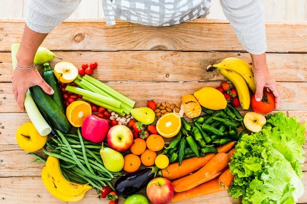 Bovenaanzicht van houten tafel vol met verse groenten en fruit van de markt voor een gezonde levensstijl zoals vegetarisch of veganistisch voor activiteiten om af te vallen