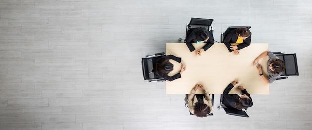 Bovenaanzicht van houten vergadertafel met zes leidinggevende zakenvrouwen die op elke stoel zitten en zaken bespreken en praten in teamwerk in de vergaderruimte.