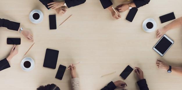 Bovenaanzicht van houten vergadertafel met zes leidinggevende zakenvrouwen die op elke stoel zitten en zaken bespreken en praten in teamwerk met mobiele telefoons op de tafel in de vergaderruimte.