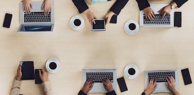 Bovenaanzicht van houten vergadertafel met zes zakenvrouwen van leidinggevenden die op elke stoel zitten met behulp van mobiele telefoons, laptops en tablet in de vergaderruimte.