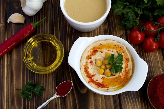 Bovenaanzicht van hummus in de witte plaat en ingrediënten op de houten tafel