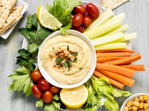 Bovenaanzicht van hummus met assortiment van groenten