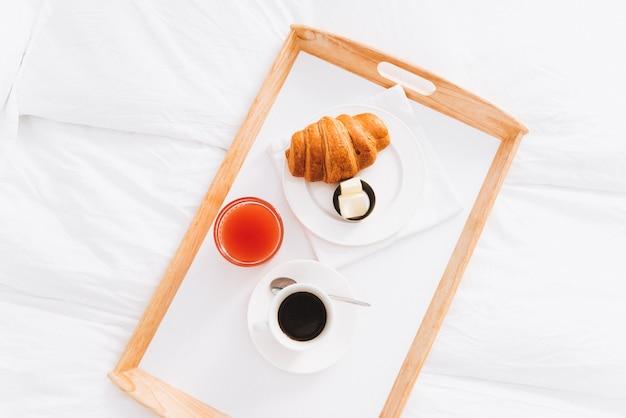 Bovenaanzicht van ideaal ontbijt op bed. koffie, grapefruitsap en croissant met boter. perfect vroege ochtend en begin van de dag.