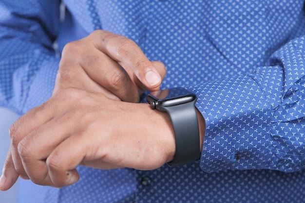 Bovenaanzicht van iemands hand met behulp van slimme horloge.