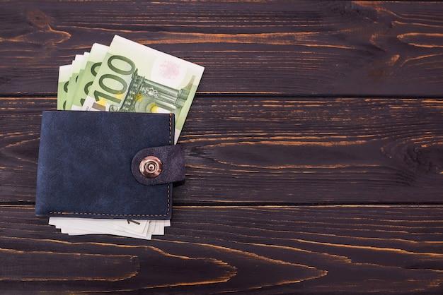 Bovenaanzicht van iemands portemonnee met eurobankbiljetten op een houten achtergrond. kopieer space.100 euro in portemonnee