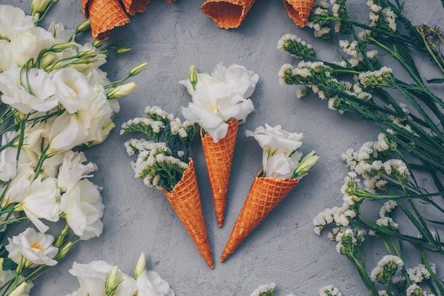 Bovenaanzicht van ijs kegels met bloemen op lichtgrijs