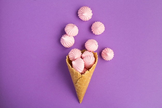 Bovenaanzicht van ijsje met roze meringue in het midden van de violette achtergrond