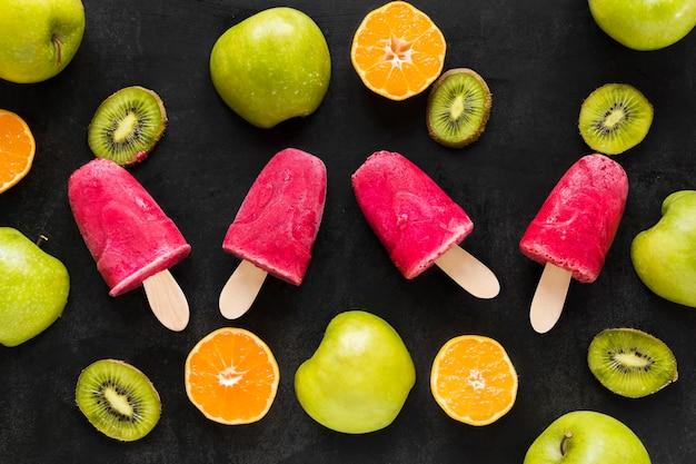 Bovenaanzicht van ijslollys met kiwi en sinaasappel