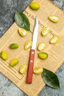 Bovenaanzicht van in tweeën gesneden verse kumquats op kranten op grijze achtergrond