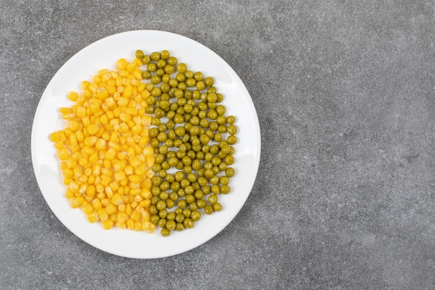 Bovenaanzicht van ingeblikt maïszaad en groene erwt op witte plaat