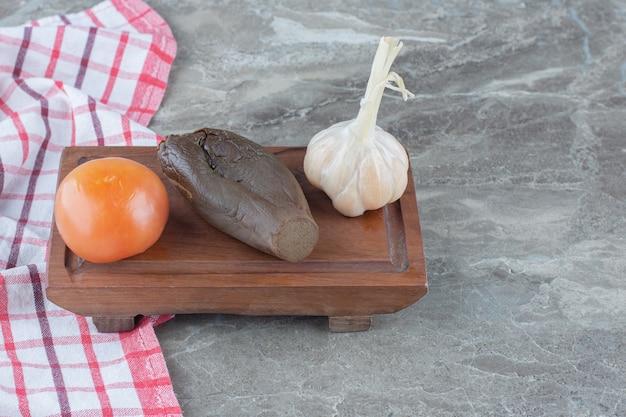Bovenaanzicht van ingeblikte groenten. tomaat, aubergine en knoflook op een houten bord.