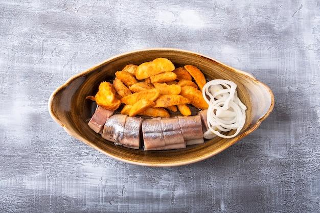 Bovenaanzicht van ingelegde haring en gebakken aardappel op een bord. kopieer ruimte