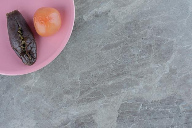 Bovenaanzicht van ingemaakte aubergine en tomaat op oranje bord over grijze achtergrond.