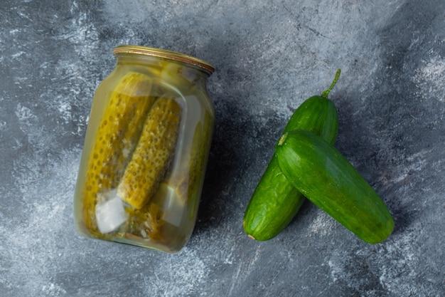 Bovenaanzicht van ingemaakte en verse komkommer.