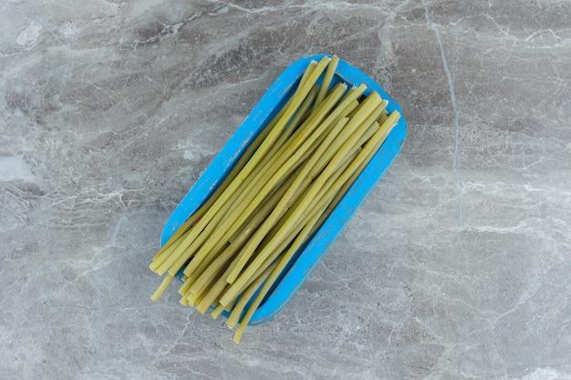 Bovenaanzicht van ingemaakte groene stok op blauwe houten plank.