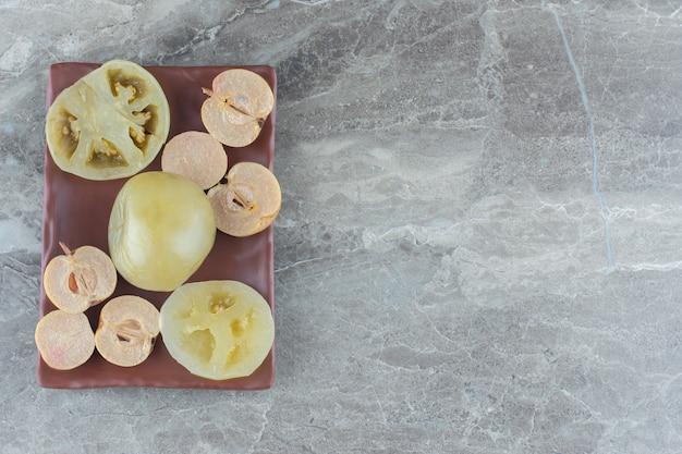 Bovenaanzicht van ingemaakte groene tomaat en appelschijfjes.