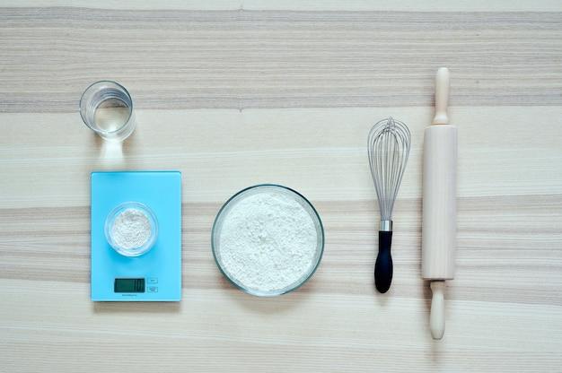 Bovenaanzicht van ingrediënten en gebruiksvoorwerpen voor het bereiden van een meel deeg, op een houten tafel met kopie ruimte