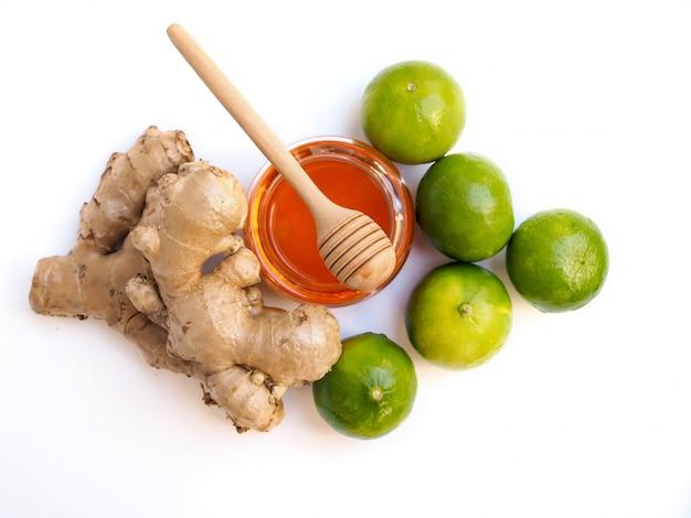 Bovenaanzicht van ingrediënten voor sapdranken of thee met honing, limoen, citroen en gember geïsoleerd op witte ruimte.