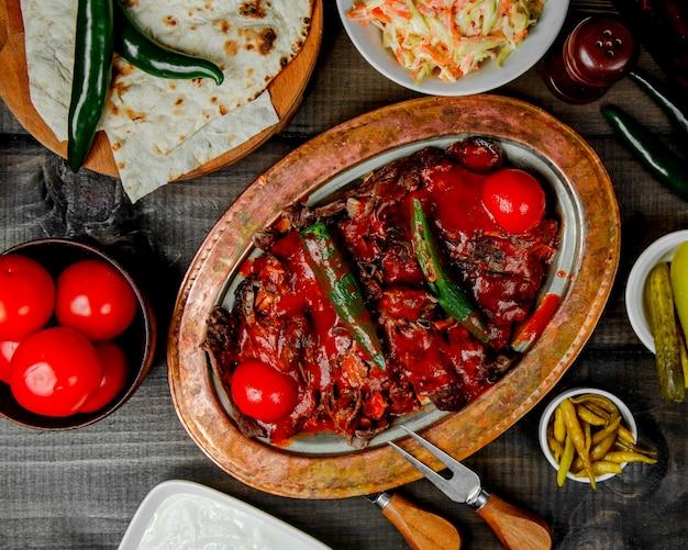 Bovenaanzicht van iskender kebab gegarneerd met peper en tomaat