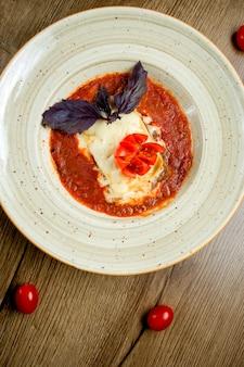 Bovenaanzicht van italiaanse lasagne plaat in tomatensaus gegarneerd met donkere basilicum