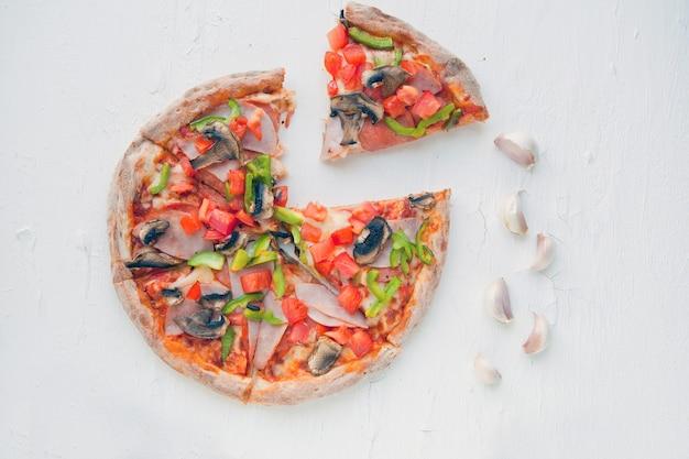 Bovenaanzicht van italiaanse pizza op witte tafel met champignons, tomaat, olijven en kaas. kijk als prosciutto, capricciosa, pizza met decoratie. foto met ruimte voor tekst. pizza met champignons op wit