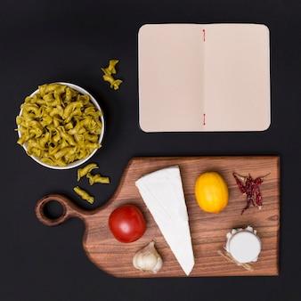 Bovenaanzicht van italiaanse rauwe pasta; gezond ingrediënt; snijplank en leeg dagboek over zwarte achtergrond