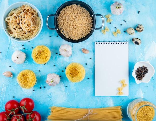 Bovenaanzicht van italiaanse rauwe pasta van verschillende soorten en vormen en gekookte stervormige pasta in een pan en spaghetti pasta in een witte kom knoflooktomaten op blauwe achtergrond