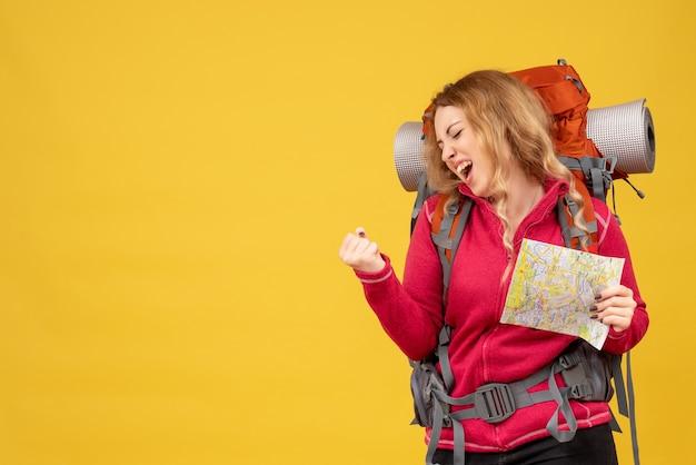 Bovenaanzicht van jong gelukkig reizend meisje in medisch masker houden en tonen kaart genieten van haar succes