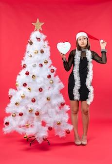Bovenaanzicht van jong meisje in een zwarte jurk met kerstman hoed staande in de buurt van de kerstboom