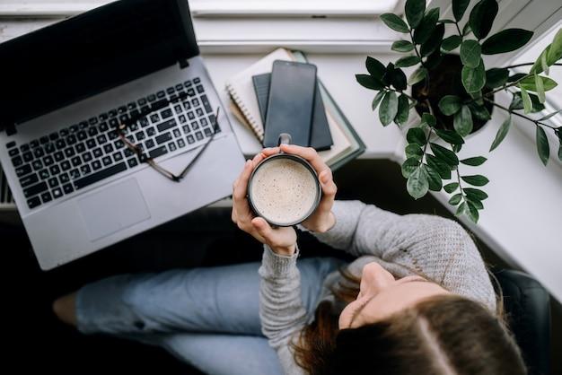 Bovenaanzicht van jong meisje in vrijetijdskleding genieten van warme koffie een pauze nemen van het werk thuis.