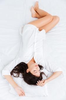 Bovenaanzicht van jonge aantrekkelijke vrouw die in bed ligt en slaapt