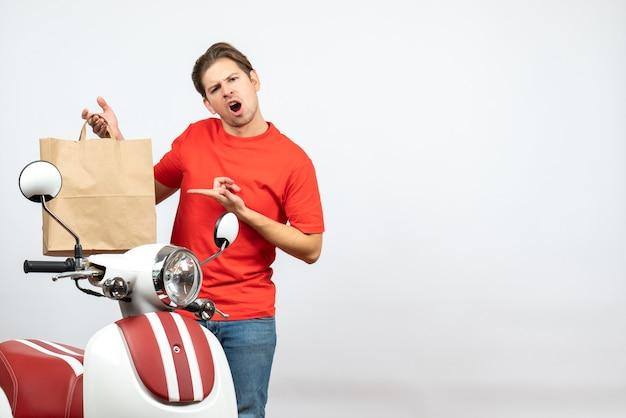 Bovenaanzicht van jonge bezorger in rood uniform staande in de buurt van scooter en geschokt voelen op de witte muur