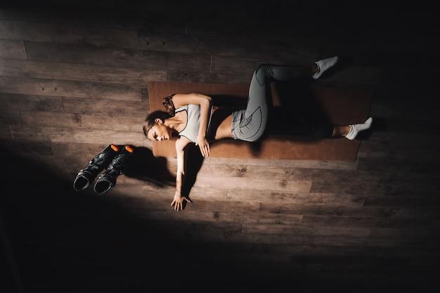 Bovenaanzicht van jonge blanke brunette liggend op mat en strekken in de sportschool 's nachts.
