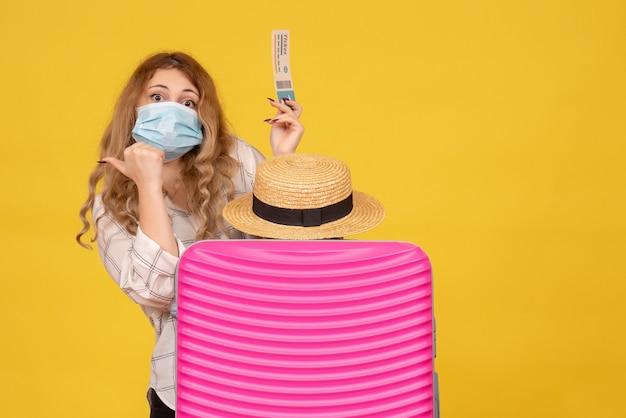 Bovenaanzicht van jonge dame die masker draagt dat kaartje toont en zich achter haar roze zak bevindt die terug wijst