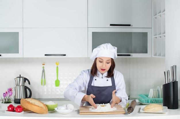 Bovenaanzicht van jonge drukke vrouwelijke chef-kok in uniform die achter tafel staat om voedsel te koken in de witte keuken