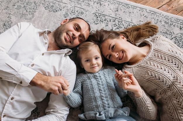 Bovenaanzicht van jonge gelukkige familie op de vloer liggen