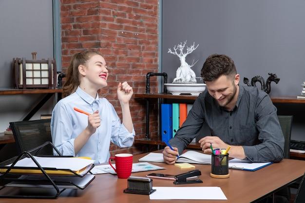 Bovenaanzicht van jonge gemotiveerde en hardwerkende glimlachende kantoormedewerkers gericht op één probleem in een kantooromgeving