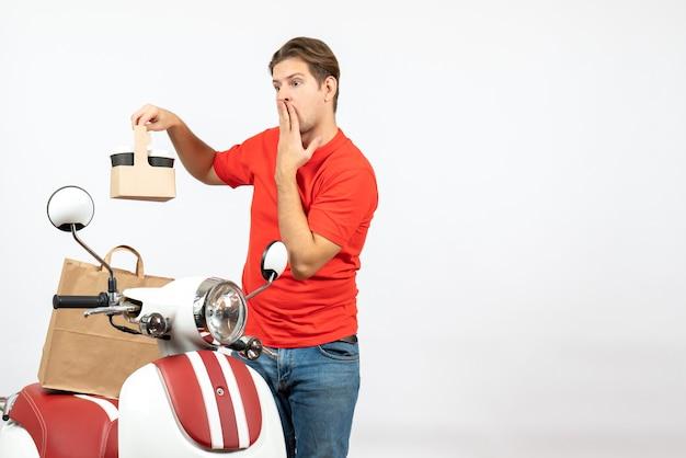 Bovenaanzicht van jonge geschokte bezorger in rood uniform staande in de buurt van scooter orde op witte muur tonen