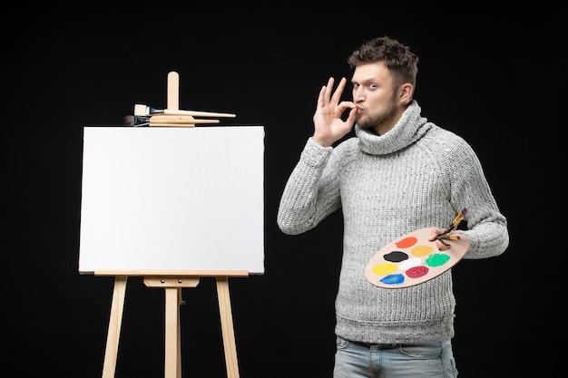 Bovenaanzicht van jonge getalenteerde ambitieuze mannelijke schilder die een brilgebaar maakt op geïsoleerde black