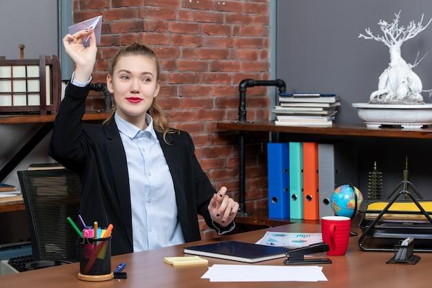 Bovenaanzicht van jonge glimlachende vrouwelijke kantoormedewerker die aan haar bureau zit en papieren vliegtuigje speelt