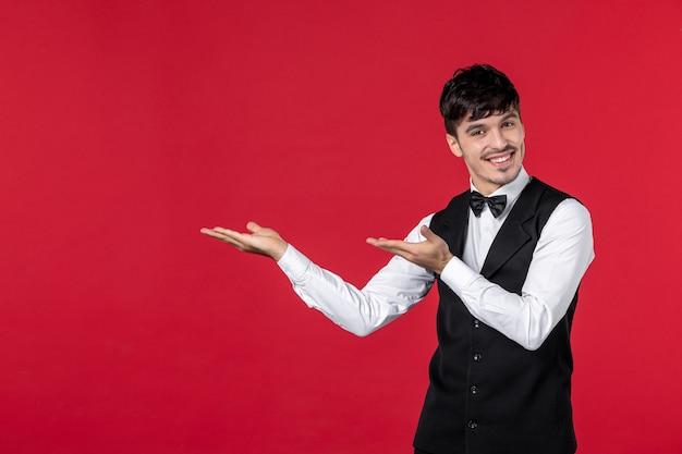 Bovenaanzicht van jonge glimlachende zelfverzekerde mannelijke ober in een uniform met vlinderdas en met beide handen naar boven gericht