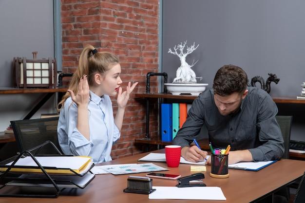 Bovenaanzicht van jonge hardwerkende, gefocuste managementmedewerkers die één probleem bespreken in een kantooromgeving