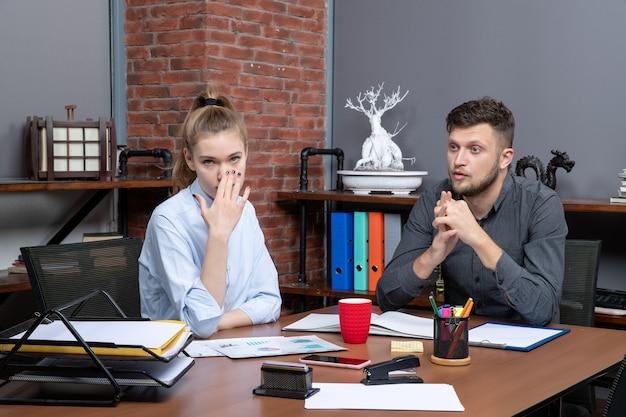 Bovenaanzicht van jonge hardwerkende kantoormedewerkers die op kantoor zitten