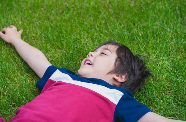 Bovenaanzicht van jonge jongen vaststelling op gazon in het park,
