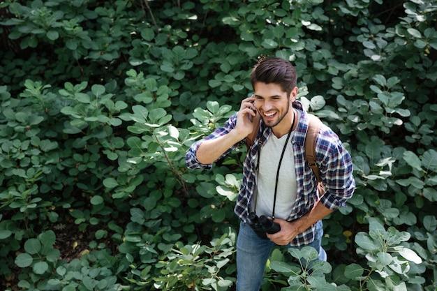 Bovenaanzicht van jonge kerel in bos in het midden van planten