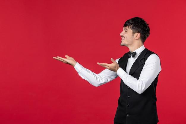 Bovenaanzicht van jonge lachende nieuwsgierige mannelijke ober in een uniform met vlinderdas en met beide handen naar boven gericht