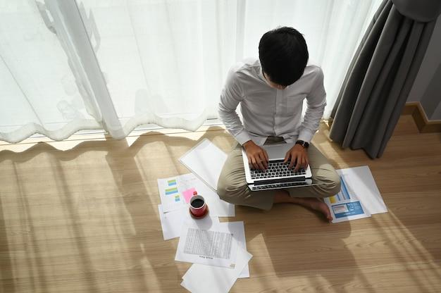 Bovenaanzicht van jonge man aan het werk te typen op laptop zittend op de vloer bij modern huis.