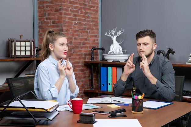 Bovenaanzicht van jonge man en zijn vrouwelijke collega die dromen in een kantooromgeving