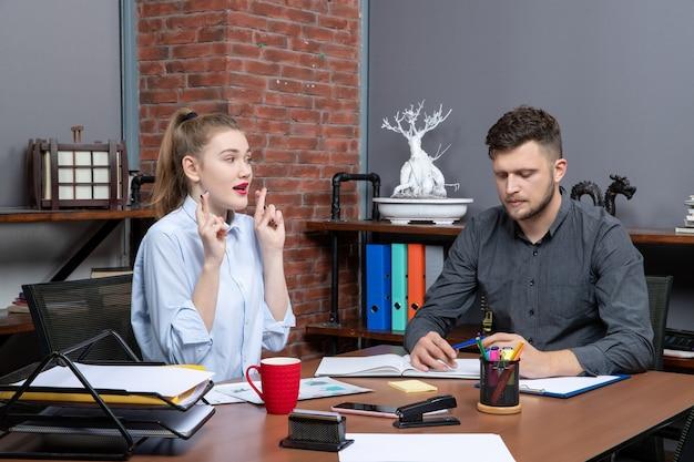 Bovenaanzicht van jonge man gericht op één probleem terwijl zijn vrouwelijke collega droomt in een kantooromgeving