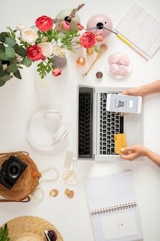 Bovenaanzicht van jonge mobiele klantenhanden met plastic kaart en smartphone zoeken en goederen in de mand toevoegen